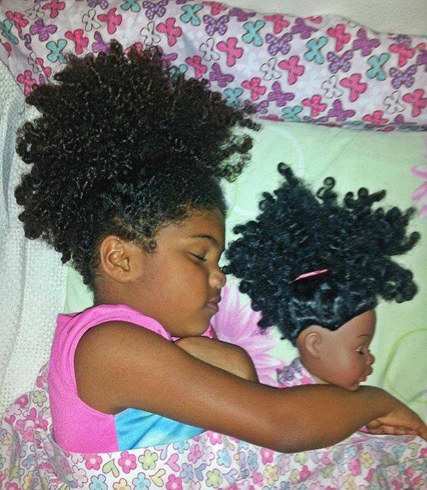niña y su muñeca recostadas en una cuna