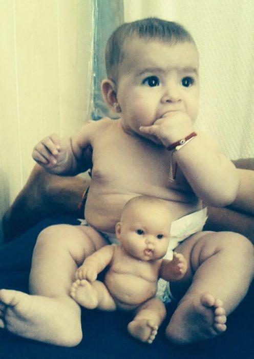 bebé que solo esta en pañal sentado frente a su muñeco que es igual a él