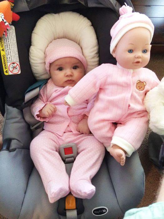 muñeca colocada junto a una bebe que esta vestida de manera similar a ella