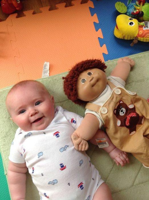 bebe recostado junto a un muñeco que se ve casi como él