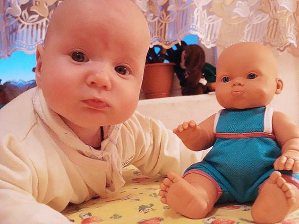 bebe que es idéntico a su muñeca, ambos se encuentran en la cama recostados