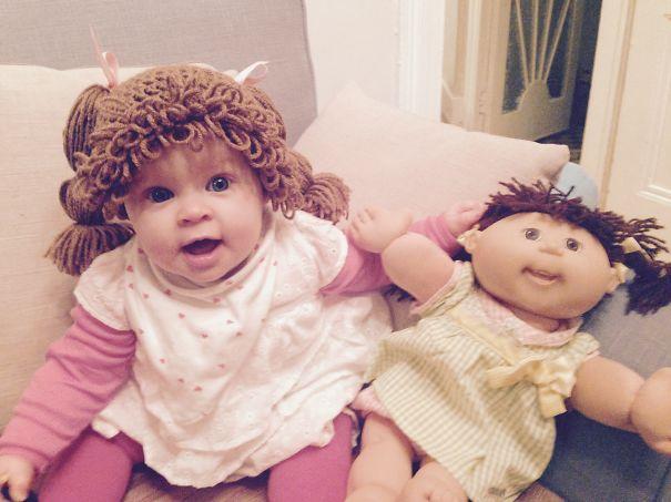 bebe usando una peluca similar a la de su muñeca mientras están sentadas en el sofá