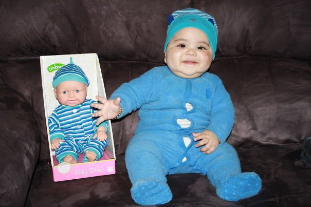bebé sentado junto a un muñeco que tiene un mameluco de color azul que es igual a él