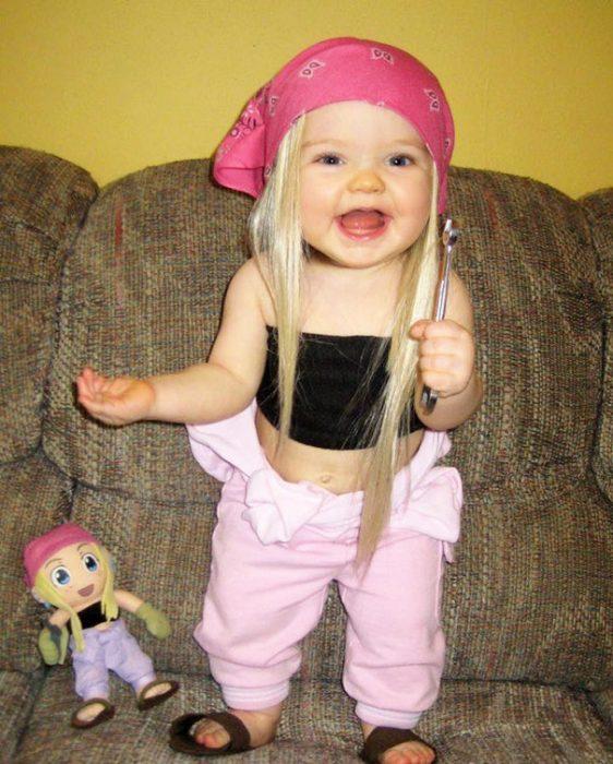 Niña recargada en un sillón vestida con un pantalón rosa, una blusca negra pañuelo y peluca en la cabeza junto a su muñeca que luce igual que ella