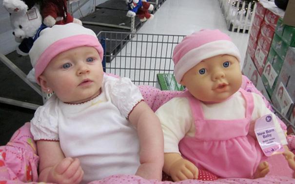 bebe sentado en un carrito de super mercado junto a su muñeca que se parece a ella