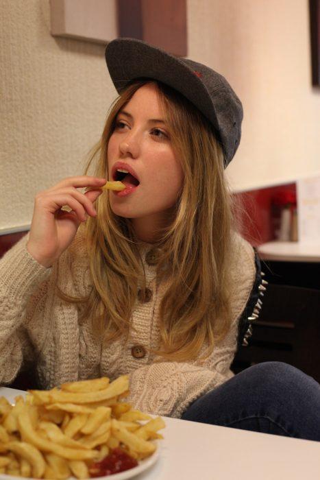 chica comiendo papas a la francesa