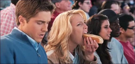 Escena de la película la cruda verdad protagonistas en un juego de beisbol comiendo