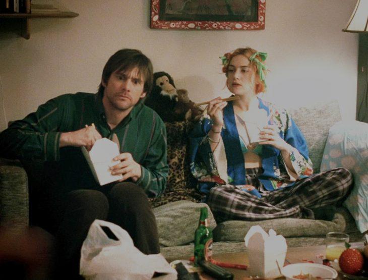 Escena de la película eterno resplandor de una mente sin recuerdos protagonistas sentados en un sofá comiendo
