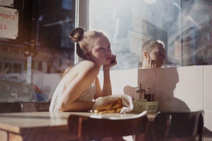 chica sentada en un restaurante comiendo y pensando