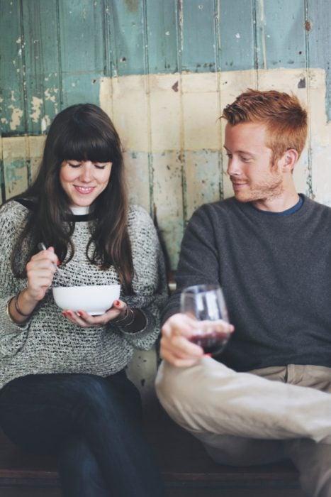 pareja de novios sentados en una silla comiendo y tomando vino