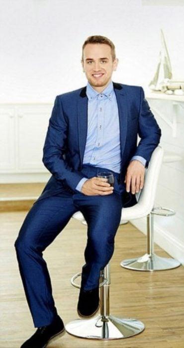 chico usando un traje azul y sentado en una silla posando para una foto