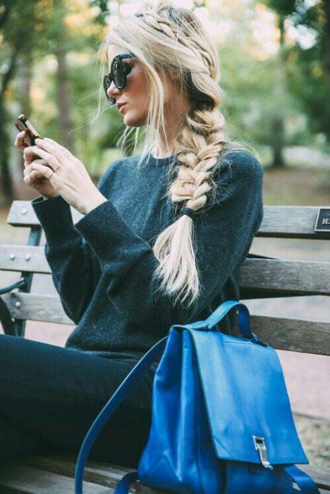 chica observando su celular en una banca del parque