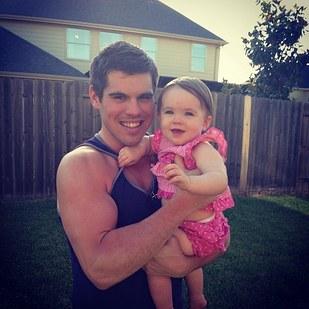 chico cargando a una bebe en su brazos mientras están parados en un patio de una casa