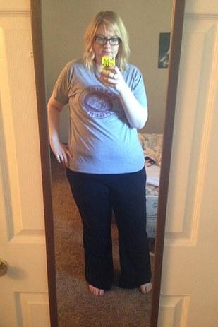 chica rubia usando una camisa gris y un pantalón negro tomándose una selfie en el espejo de su cuarto