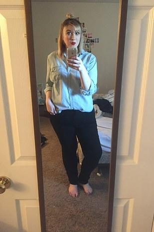 chica rubia usando una blusa de mezclilla y pantalón negro tomándose una foto frente al espejo de su cuarto