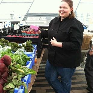 mujer gordita parada en un mercado comprando verduras