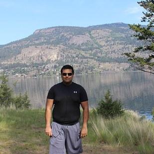 hombre parado en medio de un lago tomándose una fotografía