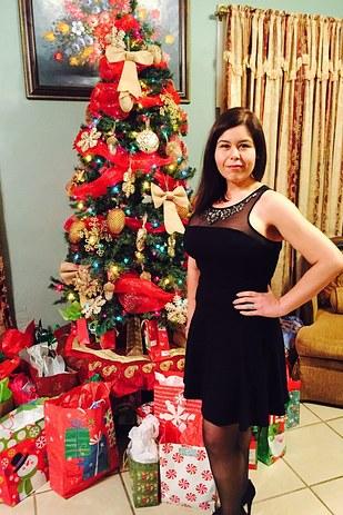 mujer usando un vestido negro parada junto a un árbol de navidad