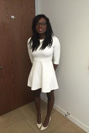 chica de color negro usando un vestido blanco parada sonriendo para una foto