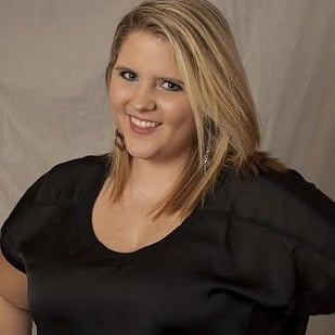 chica gordita de cabello rubio usando una camisa negra y sonriendo para una foto