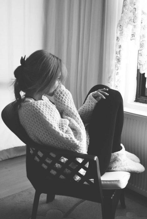 chica sentada en una silla mirando hacia la ventana pensando