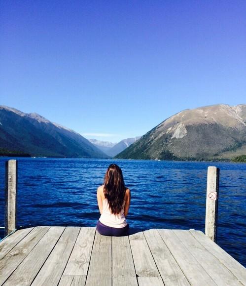 chica sentada en un muelle mirando el mar y pensando