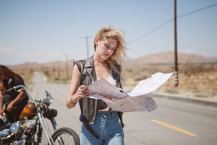 chica en una motocicleta tomando un mapa entre sus manos