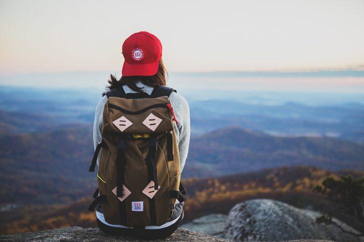chica sentada en una montaña con una mochila de viaje en su espalda