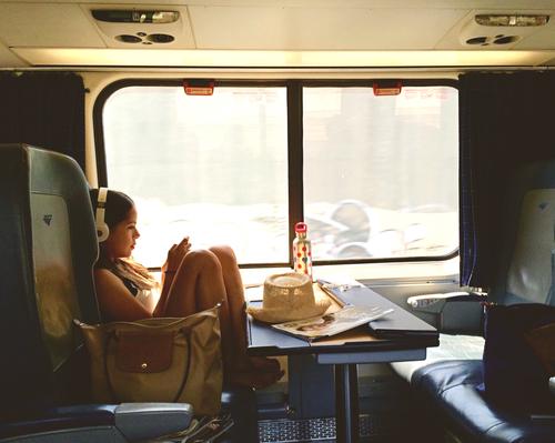 chica sentada en un tren con unos audífonos en sus orejas