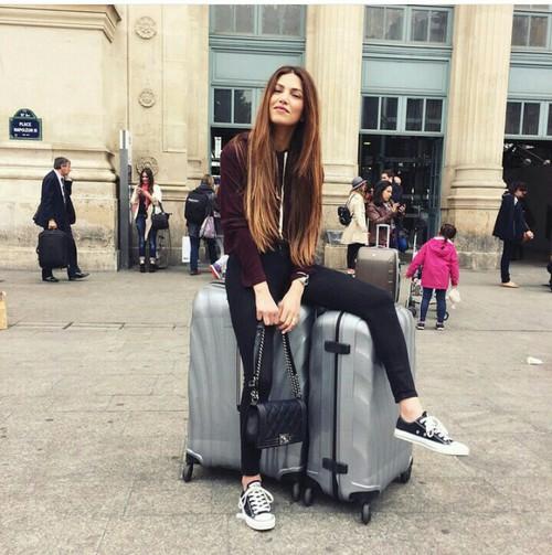 chica sentada sobre unas maletas afuera de un aeropuerto