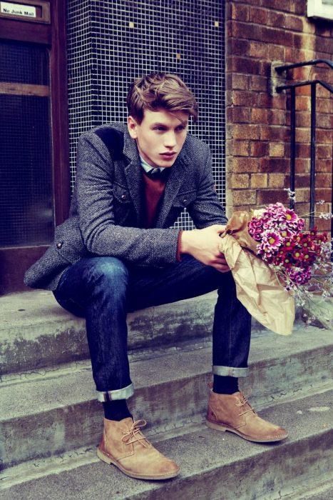 Chico sentado en unos escalones con un ramo de flores en la mano