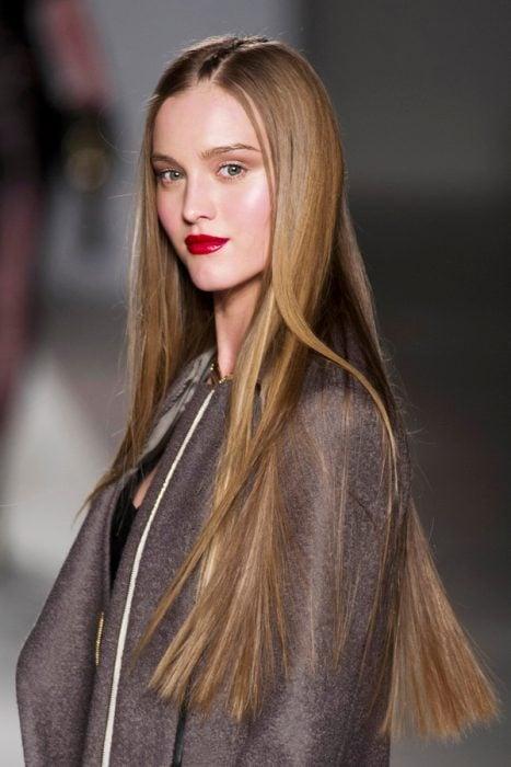 Chica con el cabello liso desfilando en una pasarela de modas