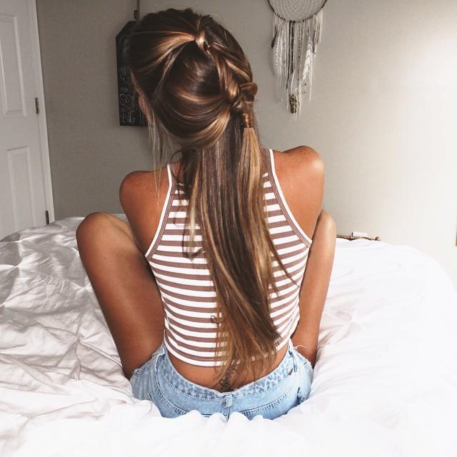 Chica sentada en la cama de espaldas con el cabello en una trenza