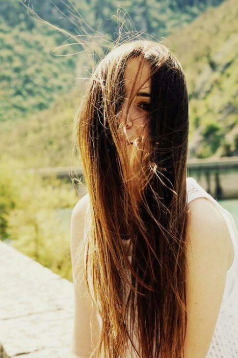chica con el cabello liso en la cara gracias al viento
