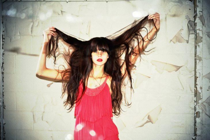 chica de cabello liso tendiéndoselo con las manos