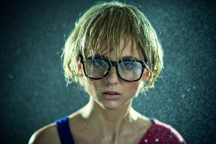 chica rubia usando lentes y  parada bajo la lluvia