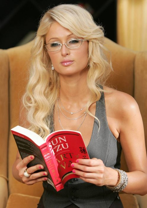 Paris hilton usando lentes sentada en un sillón leyendo un libro