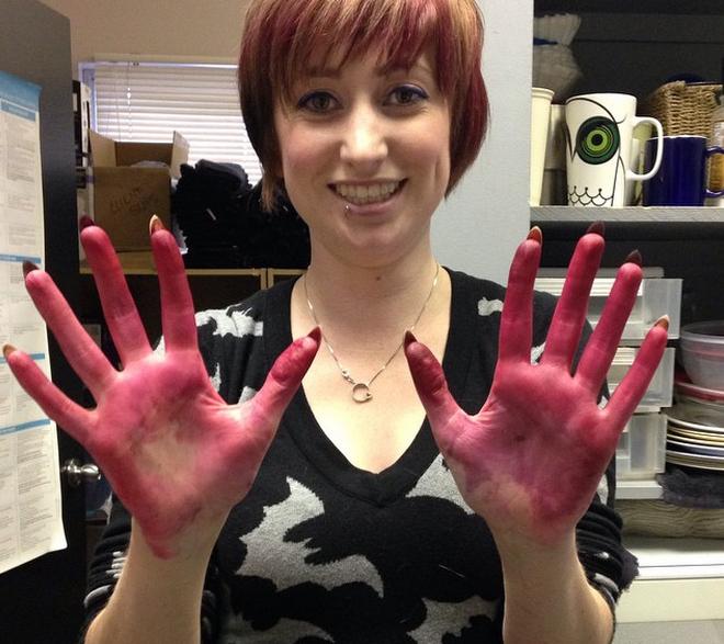 Chica con las manos llenas de pintura roja