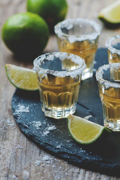shots de tequila puestos en una mesa junto con limones y sal