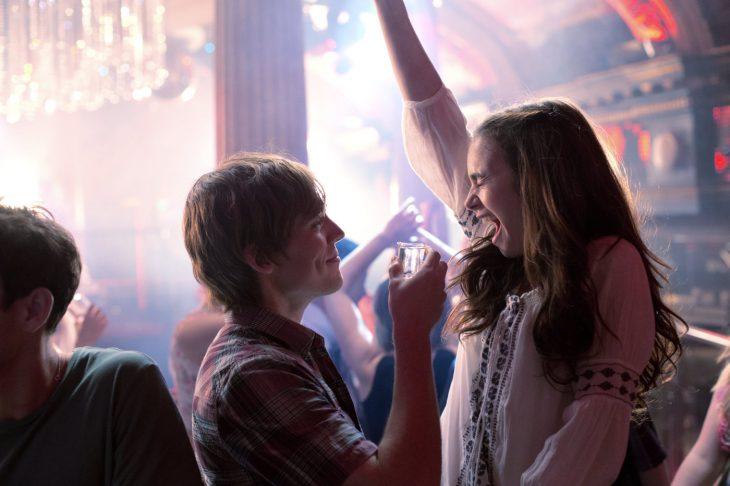 chica levantando los brasos frente a un chico con el que esta bebiendo