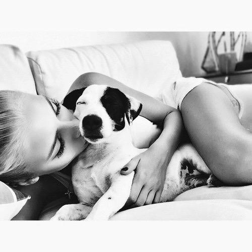 chica besando a un perrito que esta recostado con ella en la cama