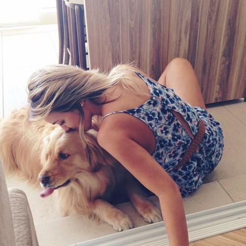 chica rubia besando a un perro que esta recostado en el suelo