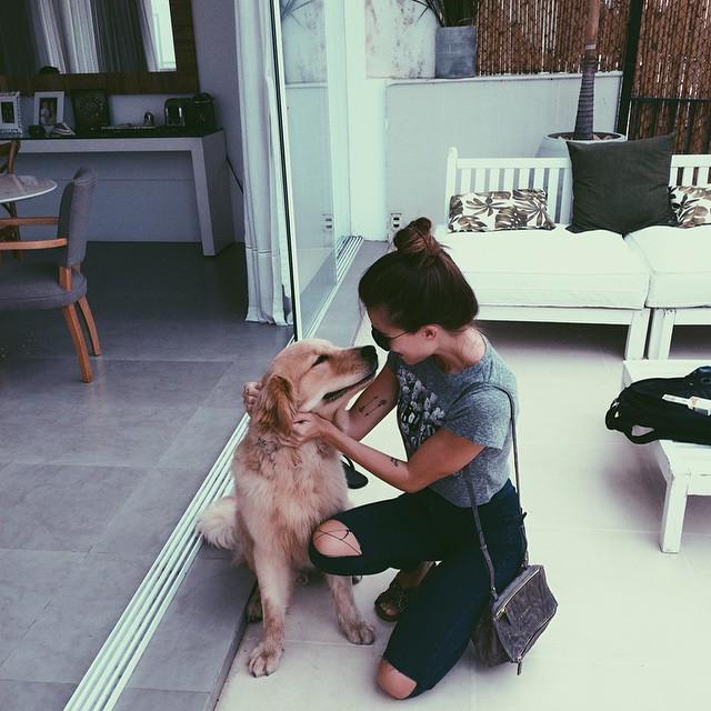 chica acariciando a un perrito en medio de la sala de una casa
