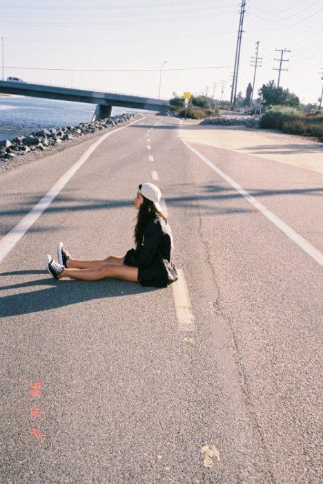 Chica sentada a media carretera