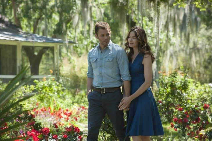James Marsden and Michelle Monagha de la película lo mejor de mi tomados de las manos caminando por un jardín