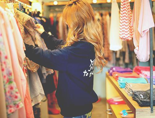 chica tomando ropa de un armario