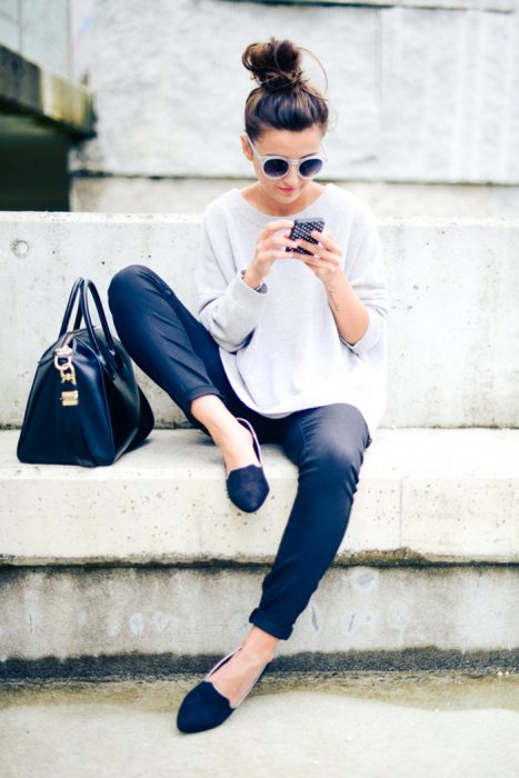 chica sentada en la banqueta de una calle enviando mensajes de texto