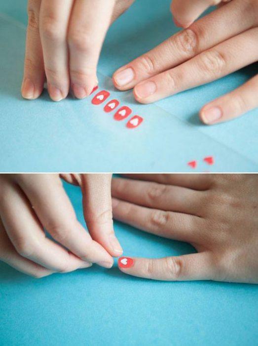 mujer sacando estampas de un papel para colocarlas en sus uñas