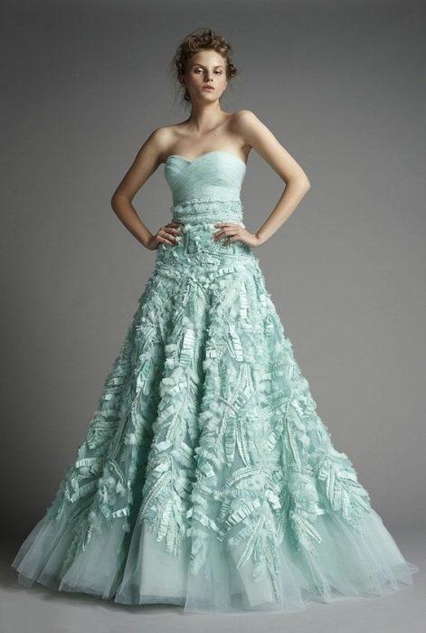 modelo usando un vestido color verde con diseños florales en el faldón