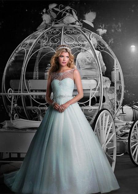 chica usando un vestido de novia color azul y parada frente a una carreta
